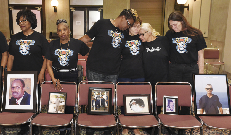 FILE – In this Feb. 10, 2017, file photo, family members of El Faro crew members stand with photographs of their loved ones during a break in a U.S. Coast Guard investigative hearing in Jacksonville, Fla. Federal accident investigators on Tuesday, Dec. 12, will determine the probable cause of the sinking of the cargo ship, the worst maritime disaster for a U.S.-flagged vessel in decades that resulted in the deaths of 33 mariners. (Bob Self/The Florida Times-Union via AP)