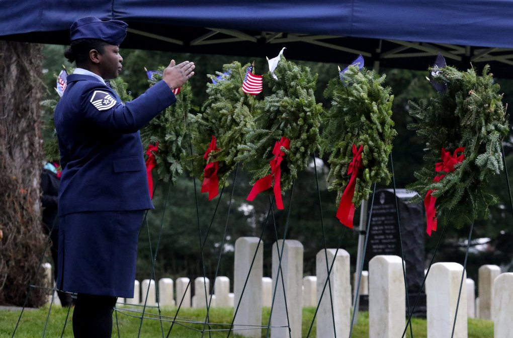 Air Force Master Sgt. Shanda De Anda salutes the wreath on which she's just placed a flag at the Wreaths Across America ceremony at veterans' graves in Evergreen Washelli on Saturday2017.  (Alan Berner/The Seattle Times)