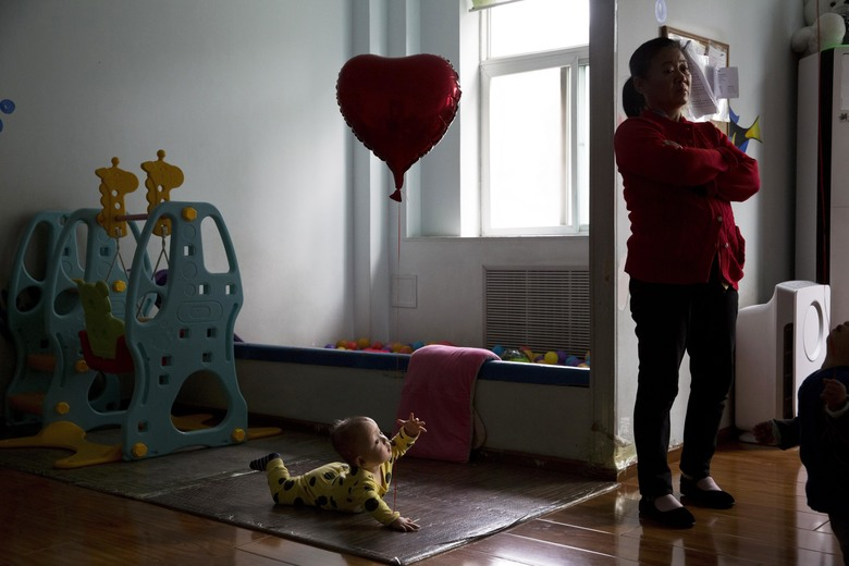 A child reaches towards a minder at a foster home of the New Hope Foundation, a charity that provides care and medical treatment for babies with deformities that can be corrected with surgery, on the outskirts of Beijing, China, on Wednesday, Oct. 11, 2017. In China, orphanages are mostly home to children abandoned by their parents and families because of medical issues including birth defects such as congenital heart disease or cleft lips or palates, or severe mental or physical disabilities. (AP Photo/Ng Han Guan)