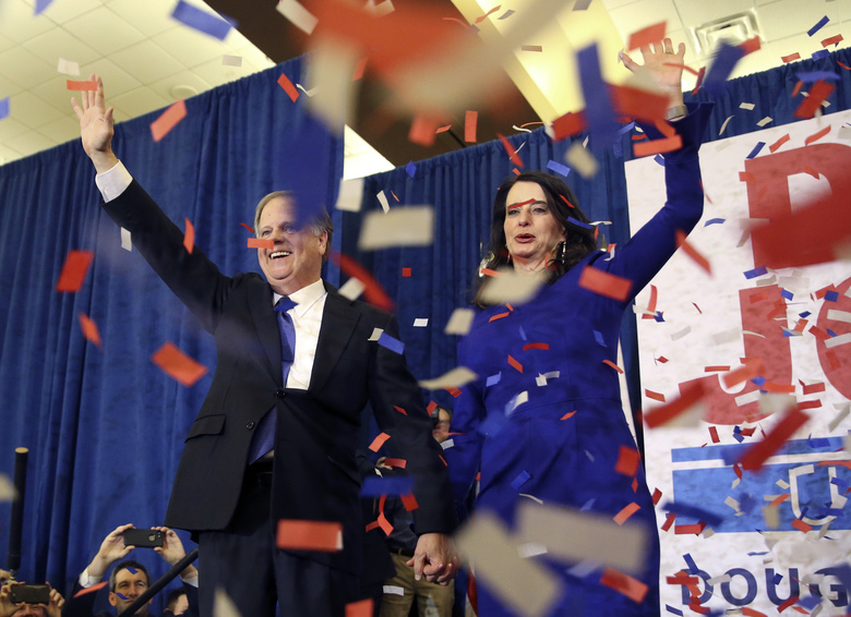Doug Jones and his wife Louise wave to supporters at Tuesday night's victory party in Birmingham, Ala. In a stunning victory aided by scandal, Democrat Doug Jones won Alabama's special Senate election. (AP Photo/John Bazemore)