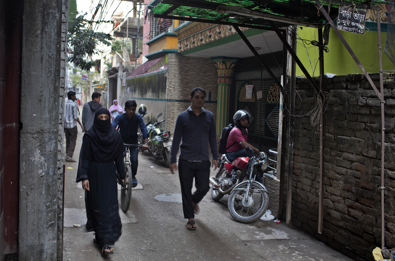 People walk past a building, on right, where 27-year-old Bangladeshi man Akayed Ullah, used to live in Dhaka, Bangladesh, Tuesday, Dec. 12, 2017. Bangladesh counterterrorism officers are questioning the wife and other relatives of Ullah, who is accused of carrying out a bomb attack in New York City's subway system, officials said Tuesday. (AP Photo/A.M. Ahad)