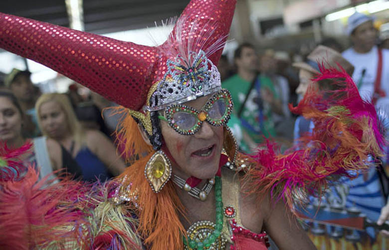 A man in a costume performs at the Central Station in Rio de Janeiro, Brazil, Saturday, Dec. 2, 2017. Hundreds of people have gathered at Rio de Janeiro's main train station for Brazil's annual Samba Day festivities. Musicians, dancers and partygoers will board trains to suburbs on the outskirts of the city to dance and sing to the rhythms of samba, the emblematic music of Carnival. (AP Photo/Leo Correa) XLC106 XLC106