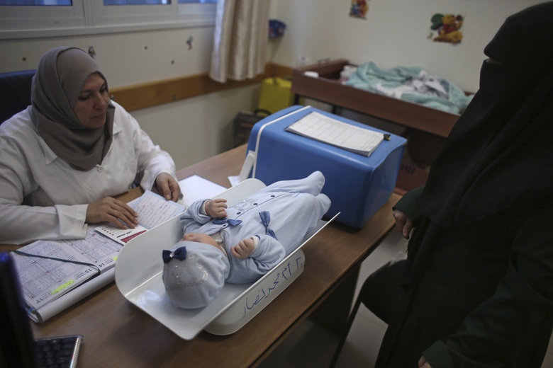 In this Sunday Jan. 14, 2018 photo, a Palestinian woman has her child checked at an UNRWA-run clinic in the Shati refugee camp, Gaza City. From the Gaza Strip to Jordan and Lebanon, millions of Palestinians are bracing for the worst as the Trump administration moves toward cutting funding to the U.N. agency that assists Palestinian refugees across the region. The expected cuts could deliver a painful blow to some of the weakest populations in the Middle East and risk destabilizing the already struggling countries that host displaced Palestinian refugees and their descendants. (AP Photo/ Khalil Hamra)