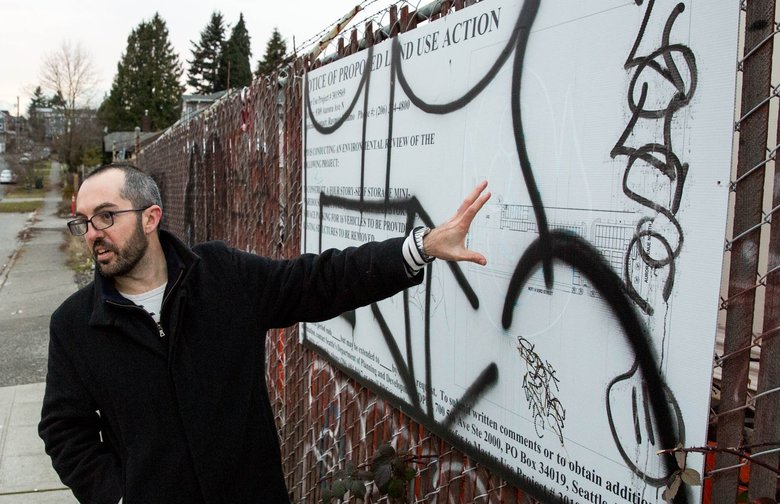 Ryan DiRaimo points at a proposed land use action sign for new developments in the Aurora-Licton Springs neighborhood of Seattle, on Thursday, Dec. 21, 2017. Seattle City Councilmember Debora Juarez advocated for making the area more walkable by passing an emergency moratorium on certain commercial development.