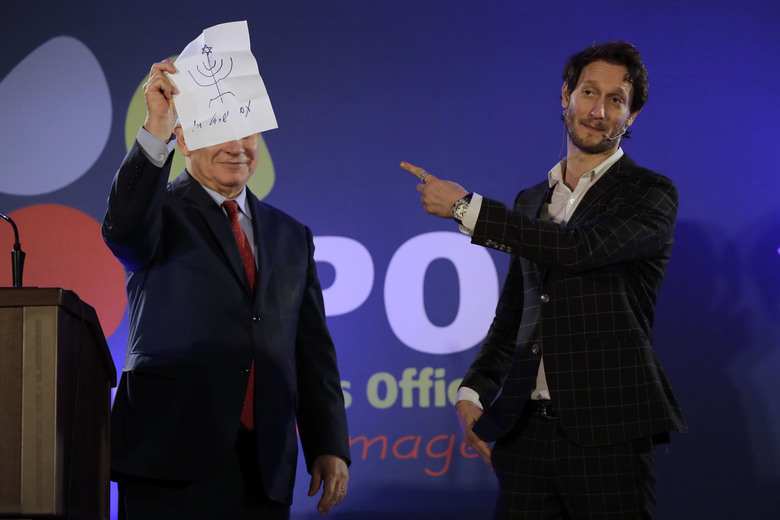 In this photo dated Wednesday, Jan. 10, 2018, Israeli mentalist Lior Suchard, right, gestures as he stands with Israeli Prime Minister Benjamin Netanyahu during the annual toast with the foreign media in Jerusalem.  Suchard went head to head with Netanyahu in front of a group of journalists, only to come up empty in an awkward duel with the Israeli leader. (AP Photo/Tsafrir Abayov)