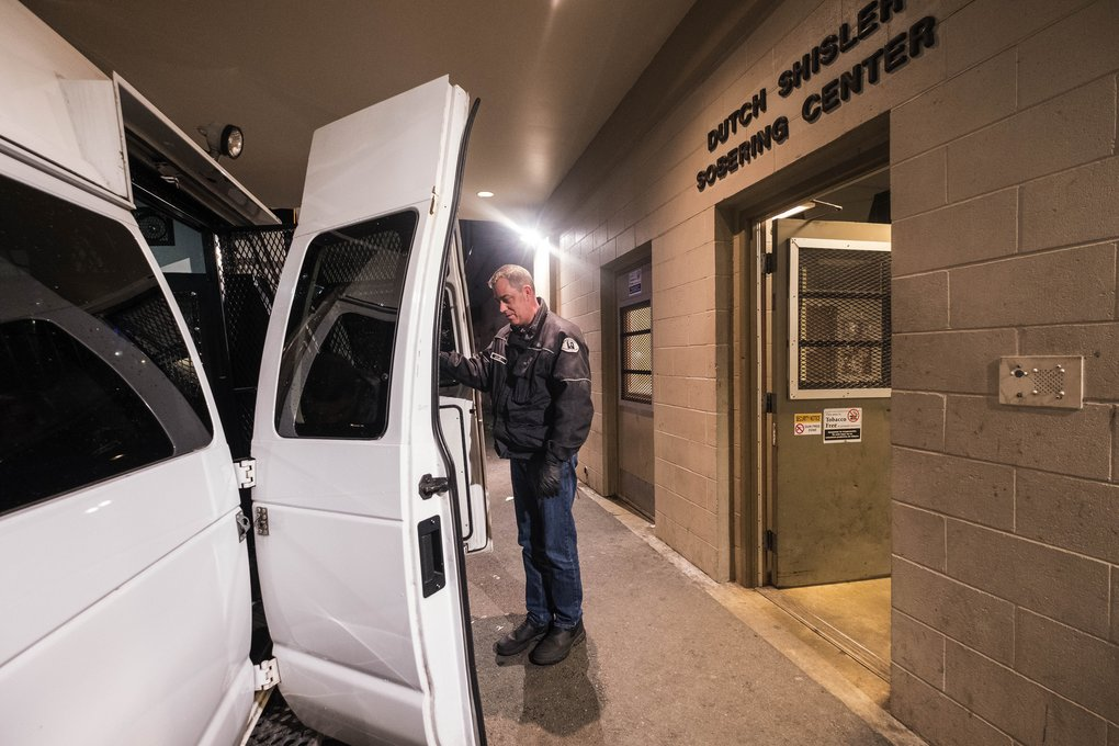 Todd Ayling helps people from the county's sober van into the Dutch Shisler Sobering Center on Boren Avenue.  (Dean Rutz/The Seattle Times)