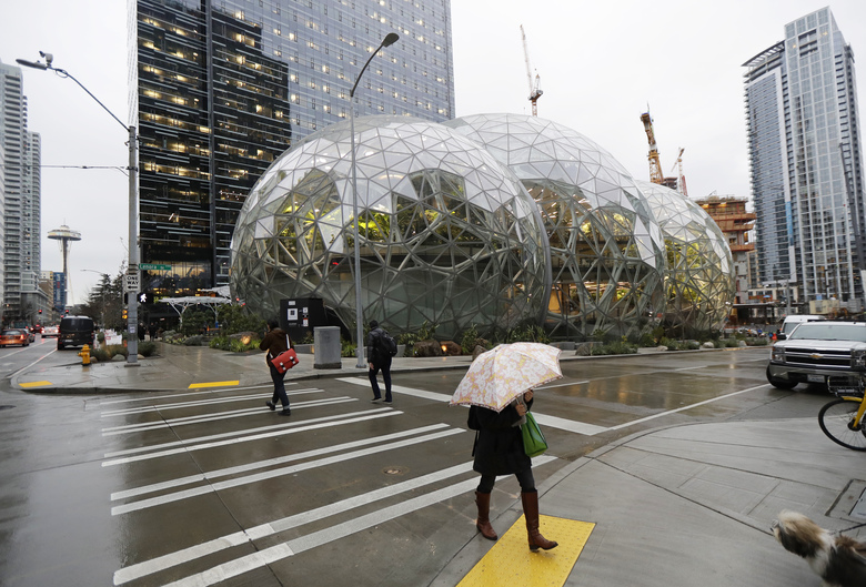 Pedestrians walk past the Amazon Spheres in downtown Seattle on Jan. 29, 2018, opening day of  the geodesic domes, which will primarily serve as a working and gathering space for Amazon.com employees. (AP Photo/Ted S. Warren)