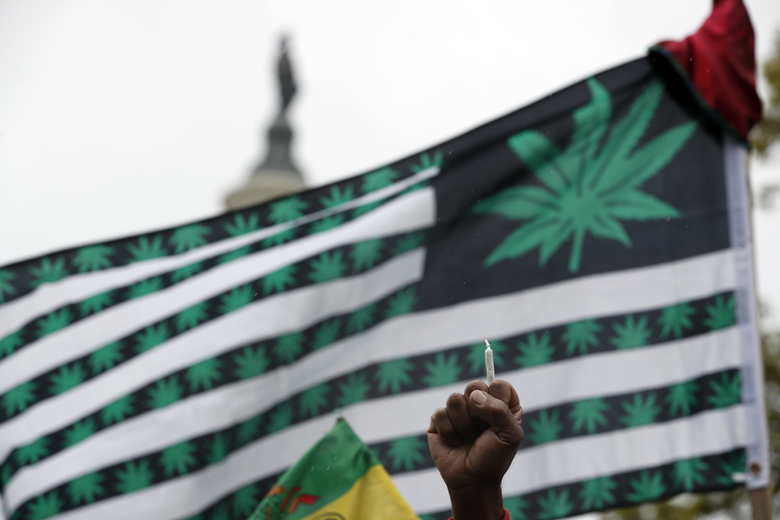 A joint is held aloft at a rally in April in Washington, D.C., to support the legalization of marijuana nationwide. U.S. Attorney General Jeff Sessions has rescinded the Obama era's hands-off approach to pot. (Alex Brandon / The Associated Press)