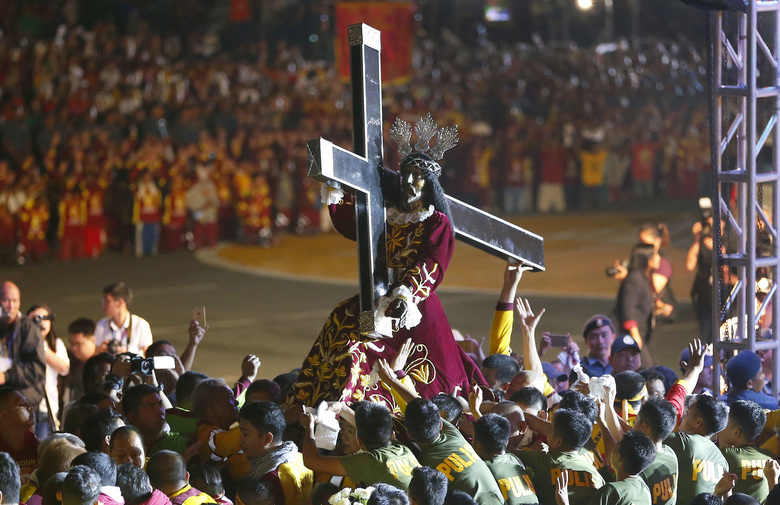 Roman Catholic devotees mount the image of the Black Nazarene on a hearse prior to a raucous procession to celebrate its feast day Tuesday, Jan. 9, 2018, in Manila, Philippines. A massive crowd of mostly barefoot Filipino Catholics joined an annual procession of a centuries-old statue of Jesus Christ under tight security amidst fears of possible attacks by Islamic extremists. (AP Photo/Bullit Marquez)