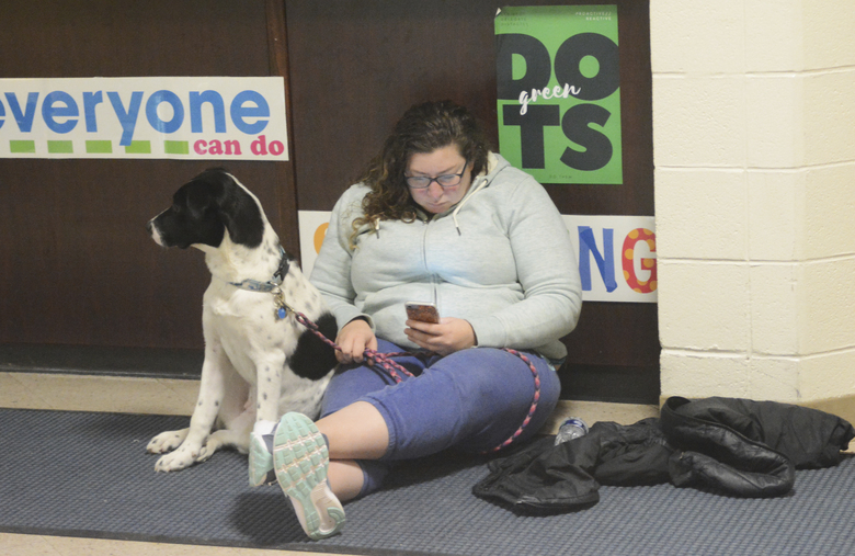 Anna Dale and her dog Poppy at about 2:30 a.m. Tuesday, Jan. 23, 2018, wait for the all-clear at Homer High School during a tsunami alert for Homer, Alaska. The city of Homer issued an evacuation order for low-lying areas shortly after an earthquake hit. (Michael Armstrong/Homer News via AP)