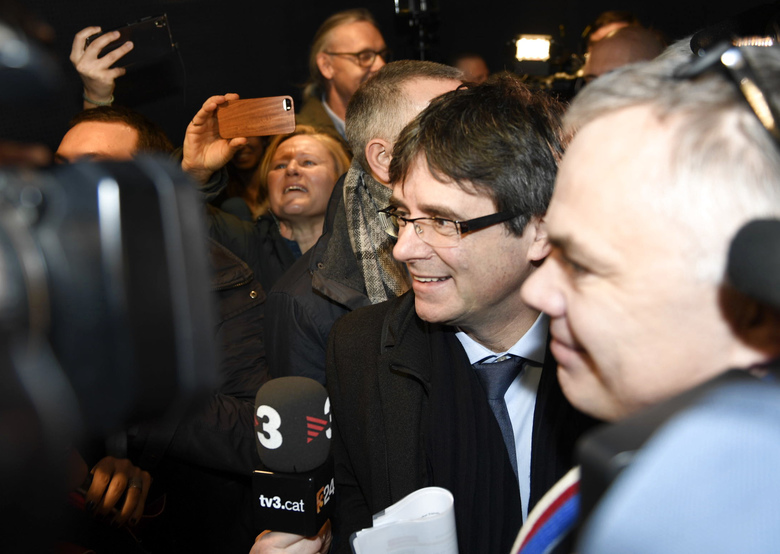 Ousted Catalan leader Carles Puigdemont, center, arrives in Copenhagen on Monday, Jan. 22, 2018. The fugitive former leader of Catalonia has arrived in Denmark, despite threats from Spain to seek his immediate arrest there. Puigdemont is being investigated by Spain over a unilateral declaration of independence by Catalonia's parliament on Oct. 27. (Tariq Mikkel Khan/Ritzau Scanpix via AP)