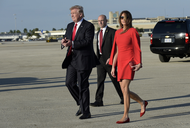 "FILE – In this Feb. 3, 2017 file photo, President Donald Trump walks with first lady Melania Trump after she greeted him on the tarmac after he arrived via Air Force One at Palm Beach International Airport in West Palm Beach, Fla. Slovenian-born Melania Trump has been unafraid to go against her husband's ""America First"" agenda, and stay true to her roots, if there's a message to be taken from her bold, foreign-flavored first lady wardrobe in 2017.  She is dressed in Givenchy.  (AP Photo/Susan Walsh)"