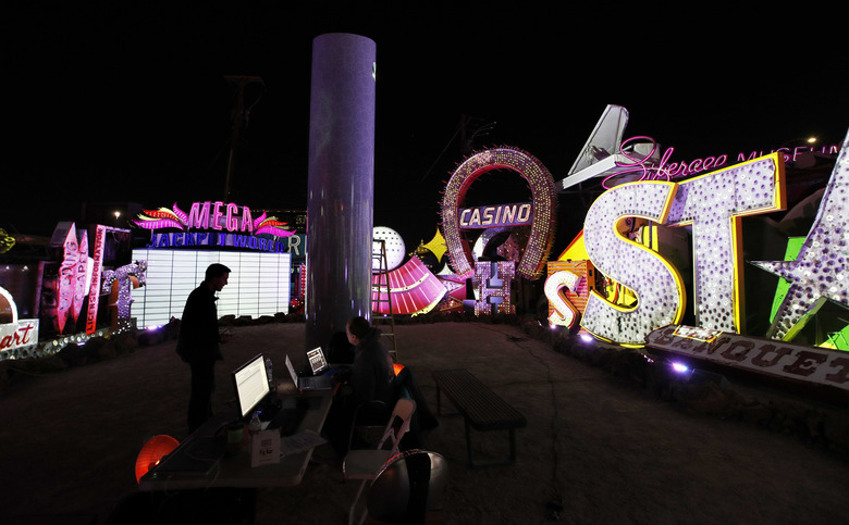 In this Jan. 24, 2018, photo, digital artist and designer Craig Winslow, left, works on an exhibit at the Neon Museum in Las Vegas. Starting this week, visitors will be able to see many of the city's classic neon signs just like they were decades ago through a type of augmented reality that projects realistic animations onto the non-working signs. (AP Photo/John Locher)