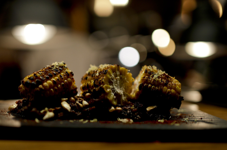 In this Nov. 17, 2017 photo, flame-cooked corn on the cob sits on a plate at Bestia restaurant in Buenos Aires, Argentina. Its co-owner, chef Nacho Trotta, traveled for weeks through Alabama, New Orleans and Texas to incorporate smoking and barbecue methods of southern cuisine. (AP Photo/Natacha Pisarenko)