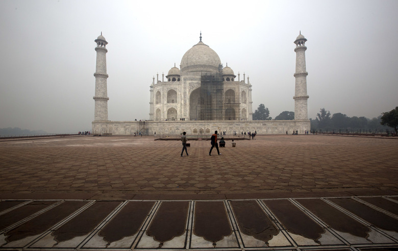 Tourists walk around Taj Mahal as workers clean the monument in Agra, India. The travel guidebook publisher Fodor's has published a list of where not to go in 2018 that includes the Taj Mahal because of a major cleaning project expected to last through much of the year.  (Manish Swarup/AP)