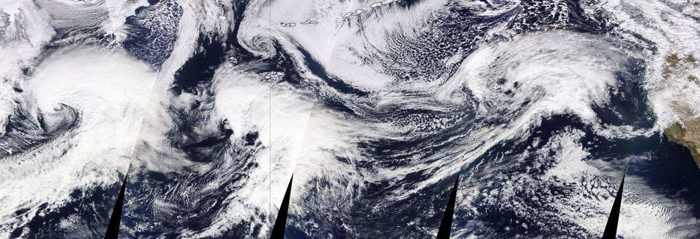A parade of storms is lined up over the Pacific Ocean, as seen in composite satellite imagery. The systems will arrive in North America over the coming days. (NASA)