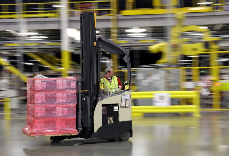 A forklift operator moves a pallet of goods at an Amazon fulfillment center in DuPont, Wash. Amazon had fewer than 10 fulfillment centers through the mid-2000s, but was nearing 100 by the end of 2017, according to a study by the Economic Policy Institute. (Ted S. Warren / The Associated Press 2015)