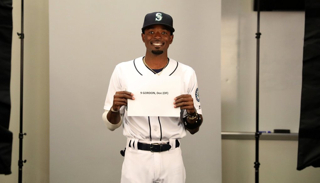 Outfielder Dee Gordon holds up his name card during Mariners photo day in Peoria, Ariz. (Ken Lambert / The Seattle Times)