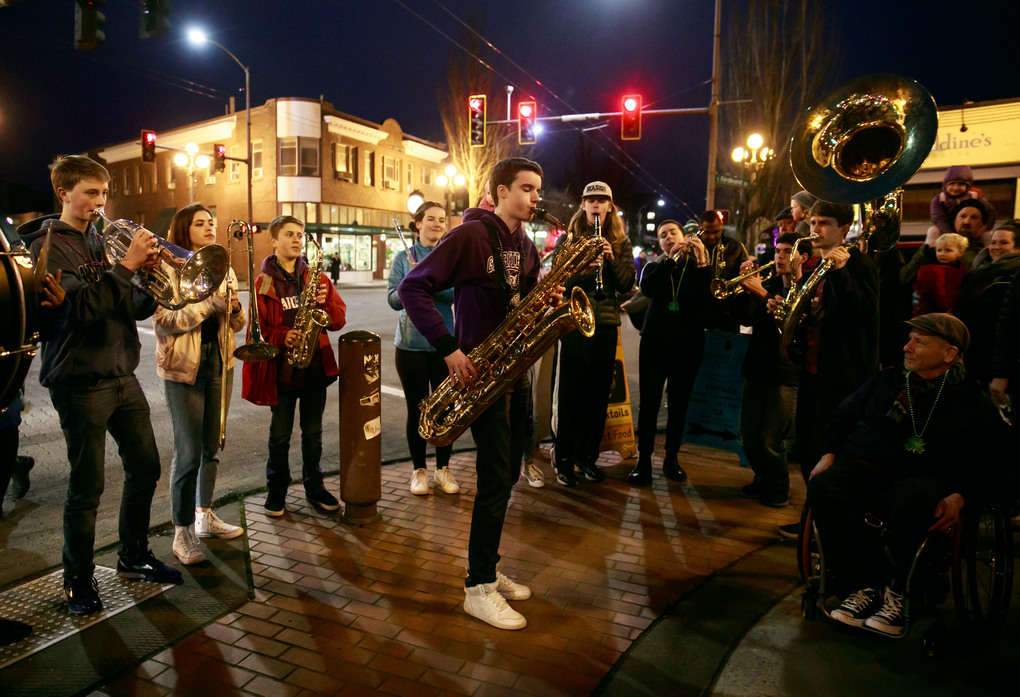 "The Garfield High School Marching Band performs outside of Lottie's Lounge on Tuesday.  Dozens of community members followed the ""second-line"" band in a procession through multiple restaurants and venues where bands played jazz, ragtime, NOLA and R&B music. (Erika Schultz/The Seattle Times)"