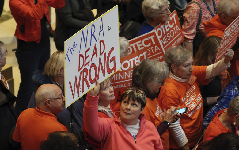 A woman holds her sign as hundreds gather in the State Capitol rotunda during a rally Thursday, Feb. 22, 2018 in St. Paul, Minn., where concerned citizens are calling for the passage of four bills they believe would substantively reduce gun violence in the state. (AP Photo/Jim Mone)