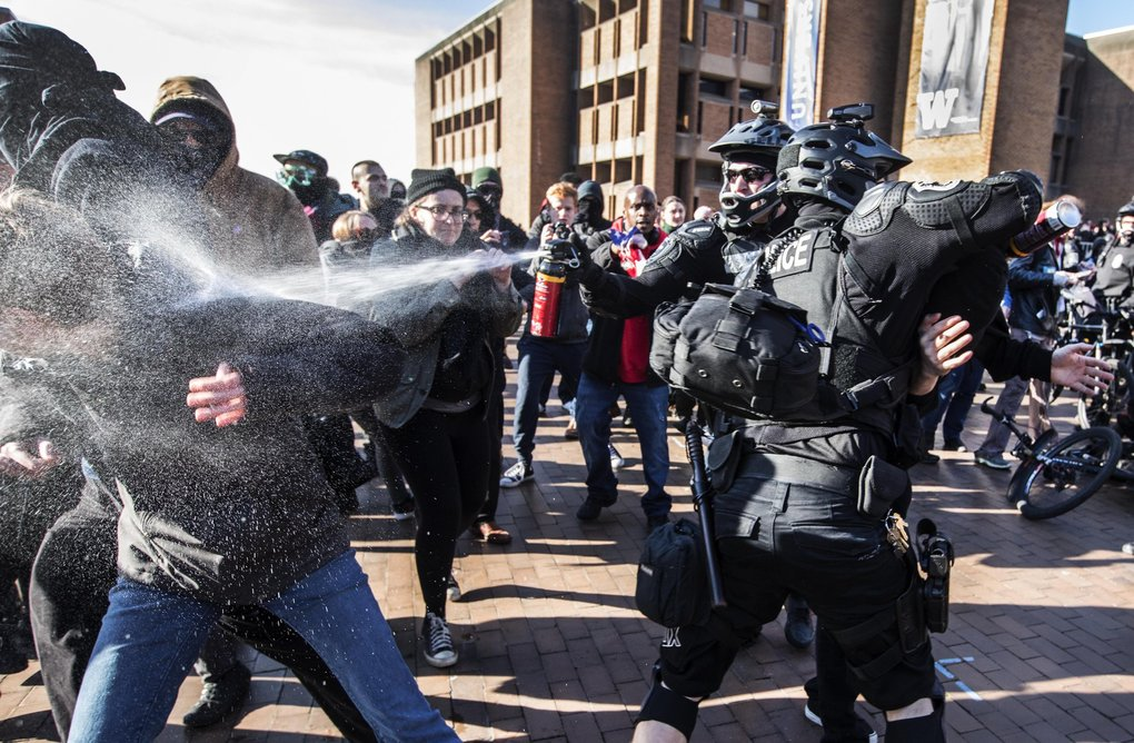 Police intervene with pepper spray during a scuffle between counterprotesters and Patriot Prayer supporters Saturday at the University of Washington's Red Square. (Steve Ringman / The Seattle Times)