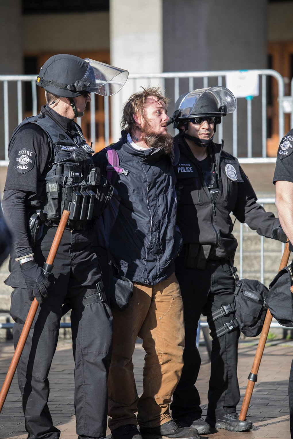 One of the counterprotesters arrested after a scuffle is taken away during the Patriot Prayer rally on the UW campus.  (Steve Ringman / The Seattle Times)