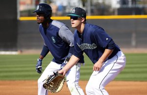 Top draft pick Evan White, right, is at first base for the Mariners, covering outfielder prospect Junior Lake, left, during a situational game exercise at spring training, Thursday, Feb. 22, 2018, in Peoria, Ariz.  205300