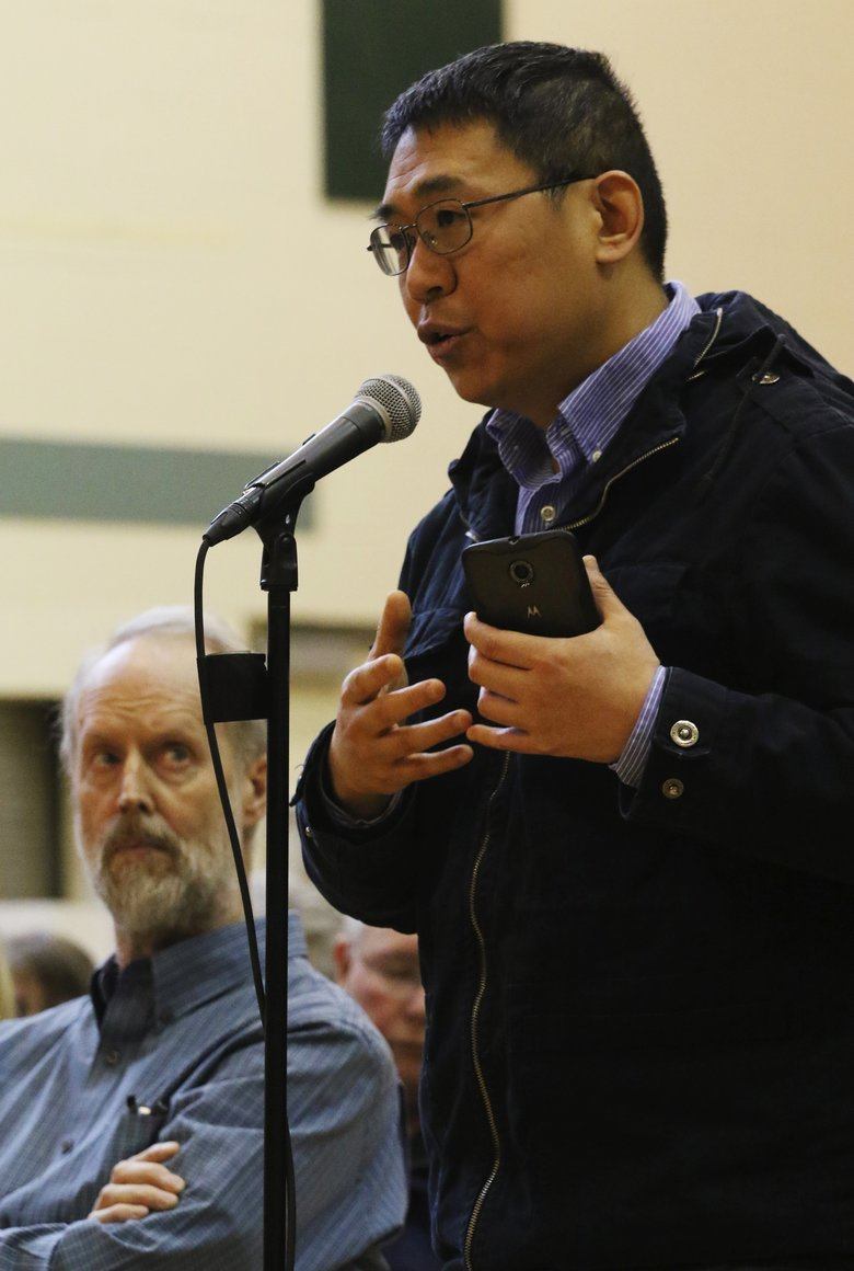 Ye Zhang addresses the town hall meeting and showed a video on his iPhone. He stated his opposition to SB 6406 and was told that the bill is dead for this session. (Alan Berner/The Seattle Times)