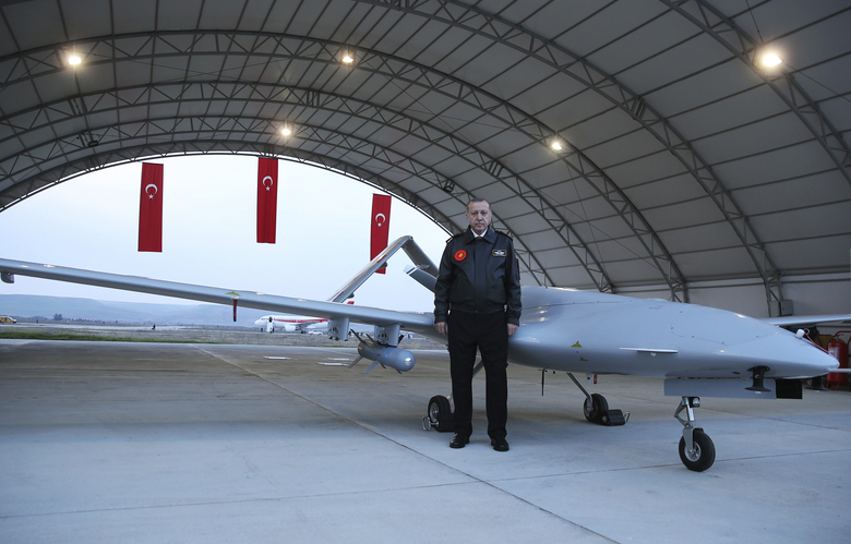 Turkey's President Recep Tayyip Erdogan poses for a photo in front of a drone at a military airbase in Batman, Turkey, Saturday, Feb. 3, 2018. The Turkish military says two of its soldiers have been killed in Syria and a third was killed on the Turkish side of the border in an attack by Syrian Kurdish militiamen, says Saturday's deaths were related to Turkey's operation against the Syrian Kurdish-held enclave of Afrin. (Murat Cetinmuhurdar/Pool Photo via AP)