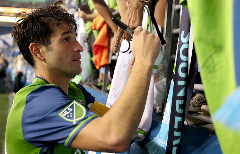 Seattle's Nicolas Lodeiro (10) signs jerseys after the Seattle Sounders FC versus Vancouver Whitecaps FC game at CenturyLink Field in Seattle Wash. Wednesday, Sept. 27, 2017. Lodeiro scored in the second half.