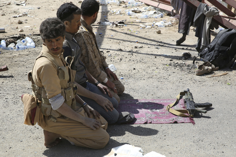 In this Friday, Feb. 2, 2018, photograph, Yemeni militiamen and a soldier allied to the country's internationally recognized government offer Friday prayers as a Kalashnikov rifle sits in front of them on the outskirts of Sanaa, Yemen. Yemen's conflict, which began as a civil war in 2014 and escalated into a regional proxy fight, drags on today. Winning the hardscrabble terrain takes time and costs dearly, only exacerbating the country's humanitarian crises and making a war that's seen over 10,000 people killed last that much longer. (AP Photo/Jon Gambrell)
