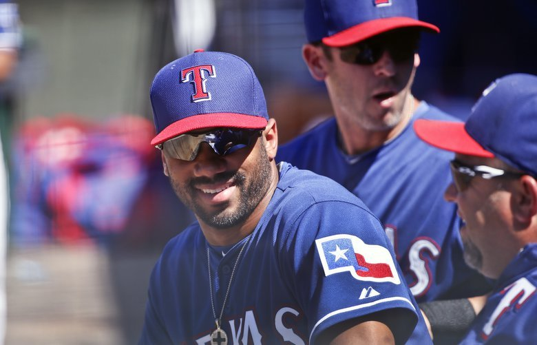 FILE – This March 28, 2015 file photo shows Seattle Seahawks quarterback Russell Wilson talking with fellow Texas Rangers in the dugout during a spring training baseball game between the Texas Rangers and the San Diego Padres in Surprise, Ariz. Wilson has been traded from the Texas Rangers to the New York Yankees. The Rangers selected Wilson in the Triple-A portion of the Rule 5 draft during the winter meetings in December 2013, about two months before he led the Seahawks to a win over Denver in the Super Bowl. (AP Photo/Lenny Ignelzi) NYPS217 NYPS217