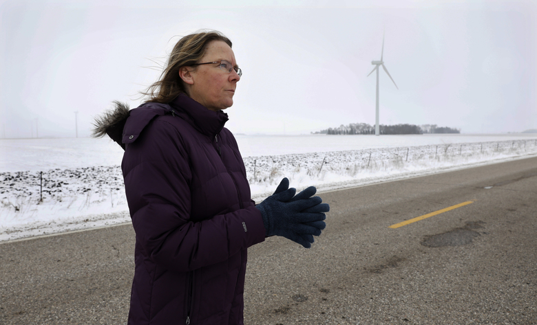 Dorenne Hansen, of Glenville, Minnesota, stands on a rural highway near a wind turbine in a field last month. Criticism by her and her neighbors has managed to stall a wind-power development.  (Charlie Neibergall/AP)