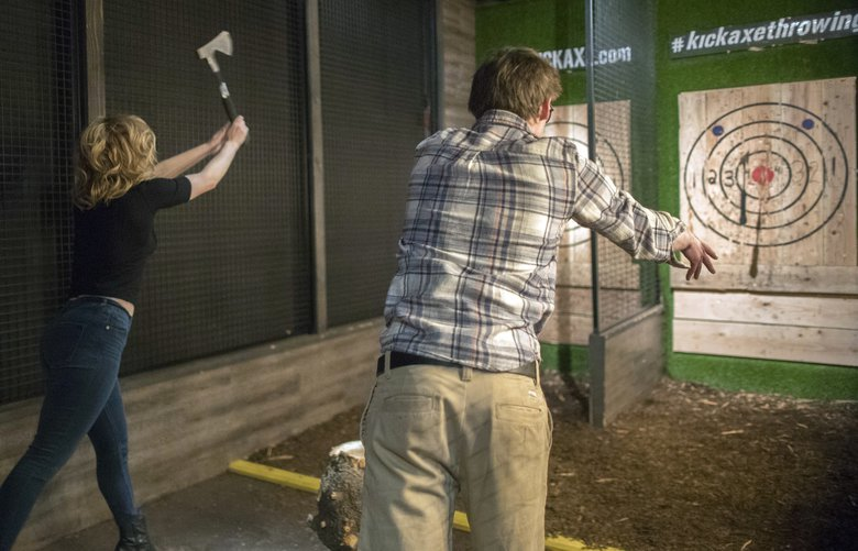 In this Saturday, March 3, 2018, photo, contestants throw hatchets at wooden bull's-eyes at the Kick Axe Throwing venue in the Brooklyn borough of New York. Kick Axe Throwing is the first bar in New York City to pick up on a nationwide trend of ax throwing. (AP Photo/Mary Altaffer) NYMA203 NYMA203