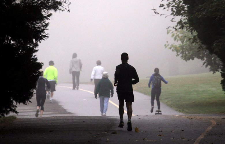 Runners, walkers, skateboarders and others head into fog as thick as pea soup at Green Lake, early Wednesday morning, Sept. 26, 2012 in Seattle. A sunny burn-off is expected soon.