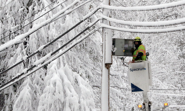 A lineman works to restore power amid limbs sagging with heavy wet snow after a snowstorm, Thursday, March 8, 2018, in Northborough, Mass.  The storm produced heavy, wet snow that brought down tree limbs and power lines. (AP Photo/Bill Sikes)
