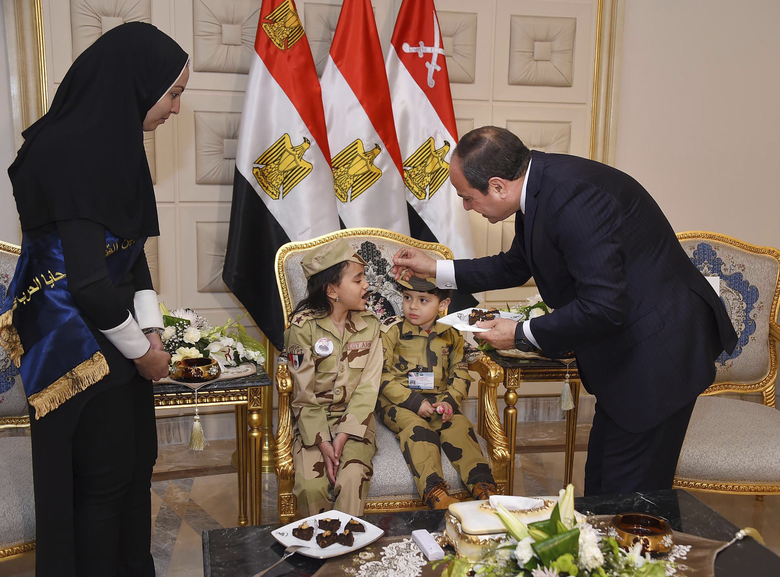 In this photo released by the Egyptian Presidency, Egyptian President Abdel-Fattah el-Sissi, right, feeds children of fallen soldiers after a conference commemorating the country's martyrs, in Cairo, Egypt, Thursday, March 15, 2018. Up for re-election in less than two weeks, Egypt's president on Thursday took center stage at a televised ceremony declaring his readiness to personally join the battle against militants and decorating soldiers and families of fallen ones. Sherif Abdel Meniom/Egyptian Presidency via AP)
