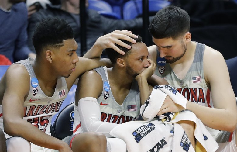 Arizona's Allonzo Trier, Parker Jackson-Cartwright and Dusan Ristic, from left, sit on the bench late in the second half of a first-round game against Buffalo in the NCAA men's college basketball tournament Thursday, March 15, 2018, in Boise, Idaho. Buffalo won 89-68. (AP Photo/Otto Kitsinger)
