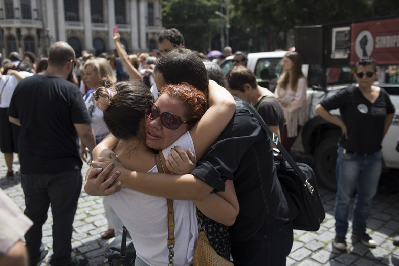 Mourners console each other as they gather in front of City Hall to pay their respects to slain council member Marielle Franco, who received four shots to her head, and her driver who were both gunned down the night before by two unidentified attackers in Rio de Janeiro, Brazil, Thursday, March 15, 2018. Police said the 38-year-old councilor, who was known for her social work in slums, was killed by perpetrators who knew exactly where she was sitting in a car that had blackout windows. (AP Photo/Leo Correa)