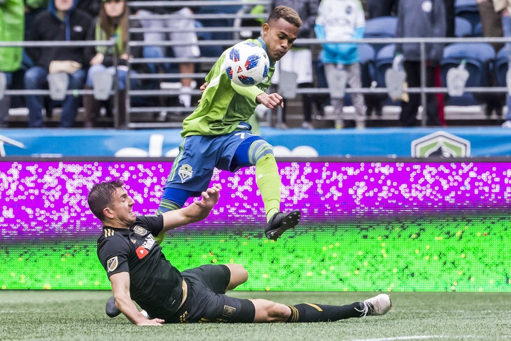 Sounders forward Handwalla Bwana passes the ball against Los Angeles defender Dejan Jakovic in Bwana's MLS debut as the Seattle Sounders FC take on Los Angeles FC for their home opener at CenturyLink Field in Seattle Sunday March 4, 2018. (Bettina Hansen / The Seattle Times)