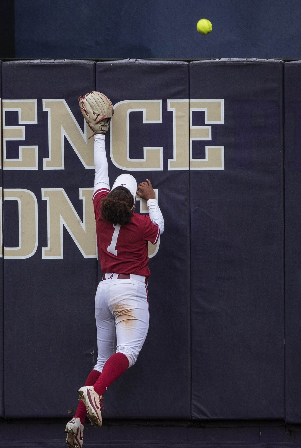 Alabama centerfielder Elissa Brown tries in vain to reel in the 2-run homer by Washington's Julia Deponte in the 1st inning Friday.  (Dean Rutz / The Seattle Times)