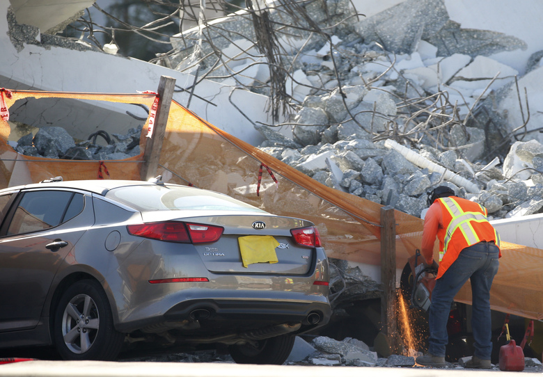 A worker uses a saw next to a crushed car under a section of a collapsed pedestrian bridge, Friday, March 16, 2018 near Florida International University in the Miami area.   The new pedestrian bridge that was under construction collapsed onto a busy Miami highway Thursday afternoon, crushing vehicles beneath massive slabs of concrete and steel, killing and injuring several people, authorities said.   (AP Photo/Wilfredo Lee)