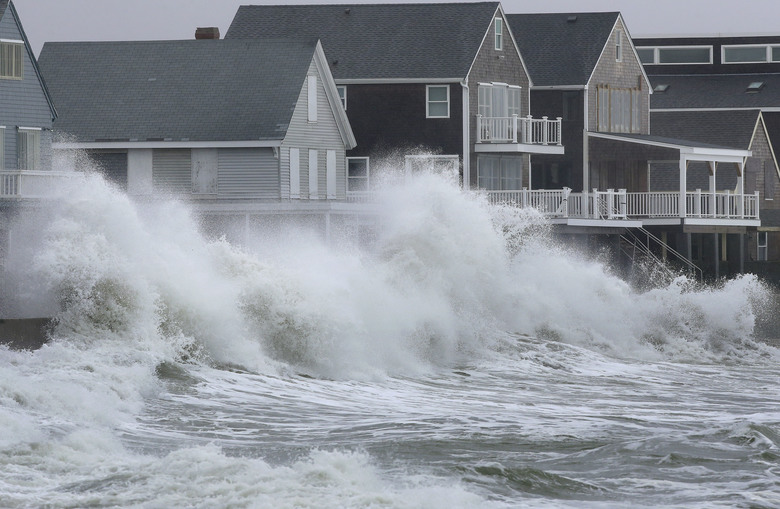 Waves crash against houses Wednesday, March 7, 2018, in Scituate, Mass. Utilities are racing to restore power to thousands of customers in the Northeast still without electricity after last week's storm as another one threatens the hard-hit area with heavy, wet snow, high winds, and more outages. (AP Photo/Steven Senne)