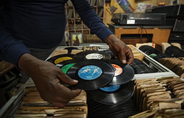 "In this photo taken Thursday, March 1, 2018, James ""Jimmy"" Rugami shows records inside his vinyl records stall in Kenyatta Market in Nairobi, Kenya. Tucked into a busy market in Kenya's capital is ""Real Vinyl Guru"", arguably the last record store still in operation in the country and which now enjoys the growing interest of music lovers who want to look beyond sleek digital offerings and return to the pleasure of browsing for a classic find. (AP Photo/Ben Curtis)"