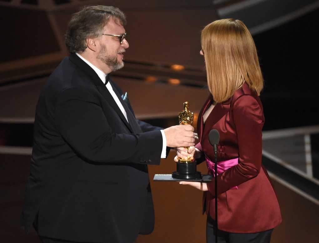 """Emma Stone, right, presents Guillermo del Toro with the award for best director for """"The Shape of Water"""" at the Oscars on Sunday, March 4, 2018, at the Dolby Theatre in Los Angeles. (Photo by Chris Pizzello/Invision/AP)"""