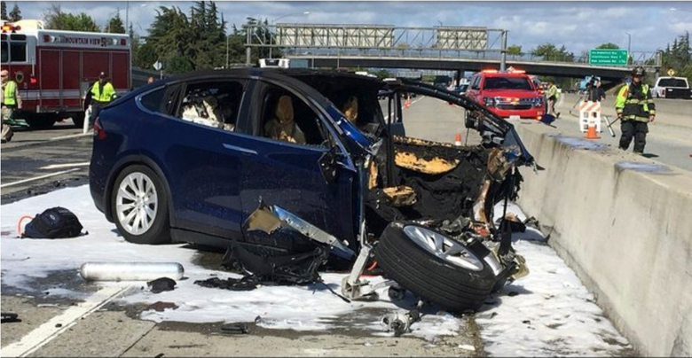 FILE – In this March 23, 2018 file photo provided by KTVU, emergency personnel work a the scene where a Tesla electric SUV crashed into a barrier on U.S. Highway 101 in Mountain View, Calif.  Tesla said the vehicle in a fatal crash last week in California was operating on Autopilot, the latest accident to involve self-driving technology. The automaker says the driver, who was killed in the accident, did not have his hands on the steering wheel for six seconds before the crash. Tesla says its Autopilot feature, which can keep speed, change lanes and self-park, requires drivers to keep their eyes on the road and hands on the wheel to take control of the vehicle to avoid accidents. (KTVU via AP)