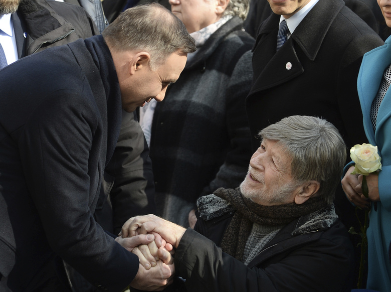 Polish President Andrzej Duda, left, shakes hands with former Israeli Knesset Speaker Shevah Weiss during ceremonies marking the 50th anniversary of student protests that were exploited by the communists to purge Jews from Poland, at the Warsaw University in Warsaw, Poland, Thursday, March 8, 2018.  (AP Photo/Alik Keplicz)