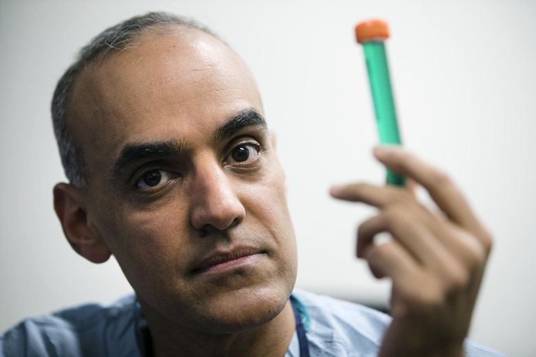 "Dr. Sunil Singhal holds a vial of fluorescent dye at the Hospital of the University of Pennsylvania in Philadelphia. With dyes, ""it's almost like we have bionic vision,"" said the surgeon. ""We can be sure we're not taking too much or too little.""  (Matt Rourke/AP)"