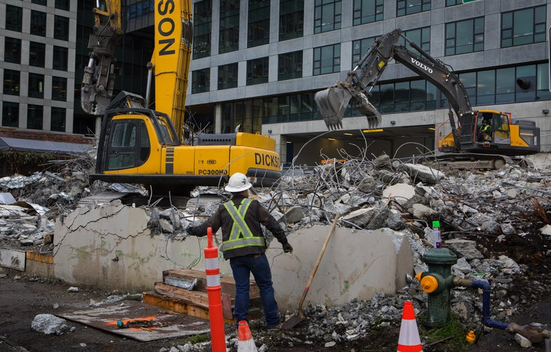 Construction appears to be starting to slow in Seattle. Cleanup is underway Monday on a building recently torn down at the corner of Thomas Street and Terry Avenue North in Seattle's South Lake Union neighborhood. (Ellen M. Banner/The Seattle Times)