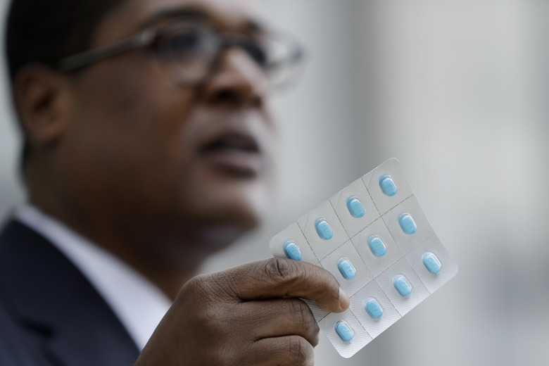 Bill Cosby's spokesman Andrew Wyatt holds up a package of Benadryl tablets as he speaks to the media during a break in Cosby's sexual assault trial, Tuesday, April 17, 2018, at the Montgomery County Courthouse in Norristown, Pa. (AP Photo/Matt Slocum)